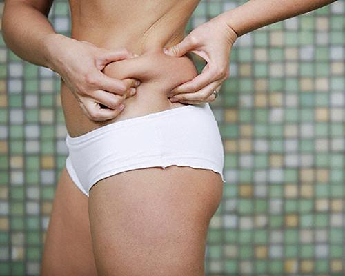 Woman Grabbing Fatty Skin on Waist --- Image by © Tim Pannell/Corbis